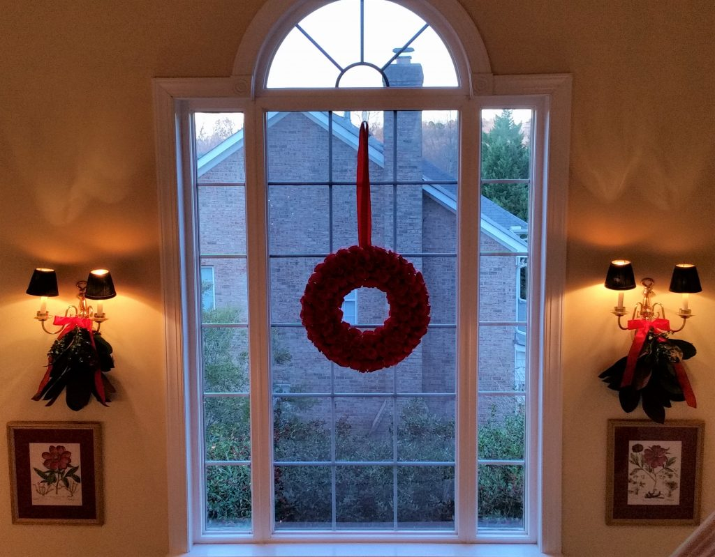 Stairwell window with red rose curl wreath. Sconces are decorated with fresh magnolia and boxwood swags.