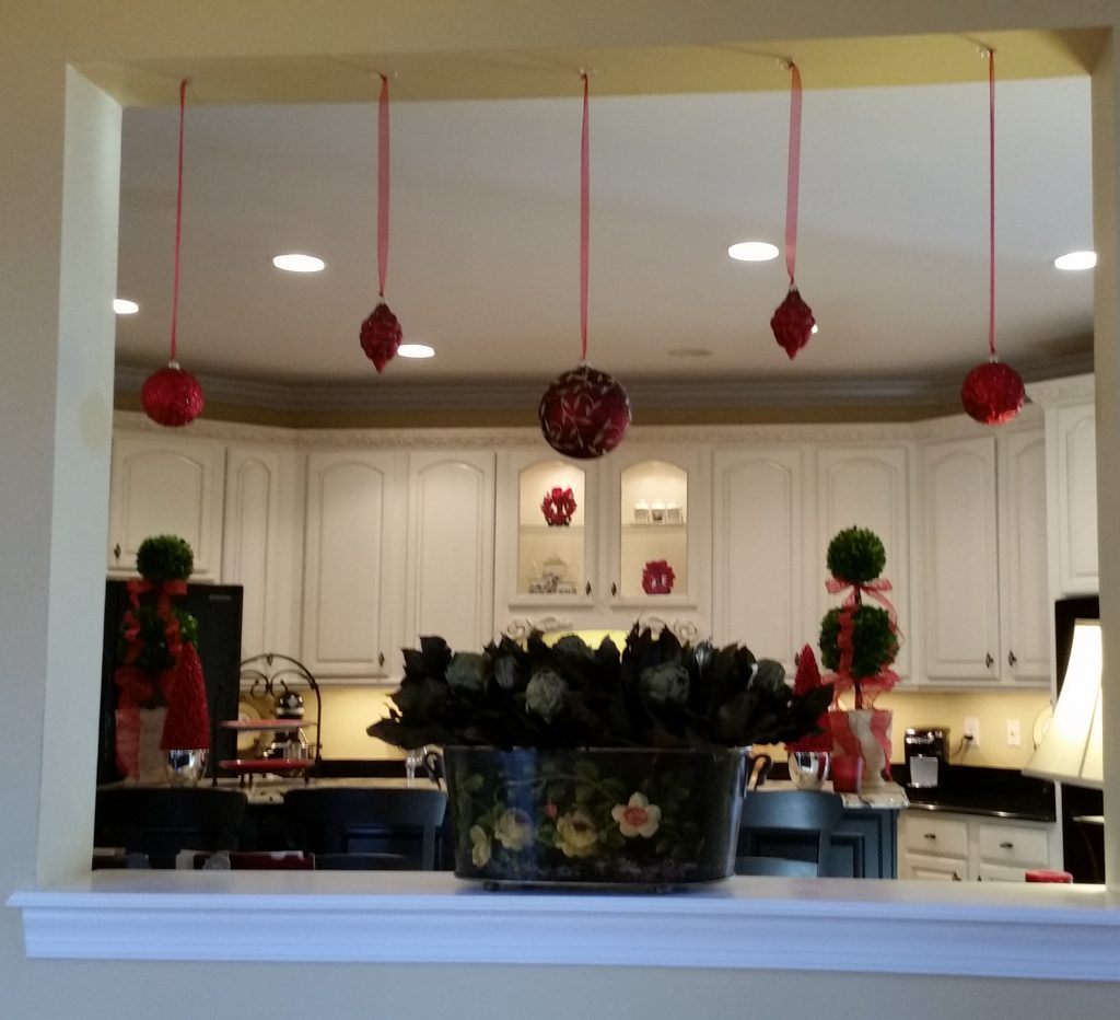 Christmas ball suspended by delicate sheer ribbon in the pass-thru between the family room and the kitchen.
