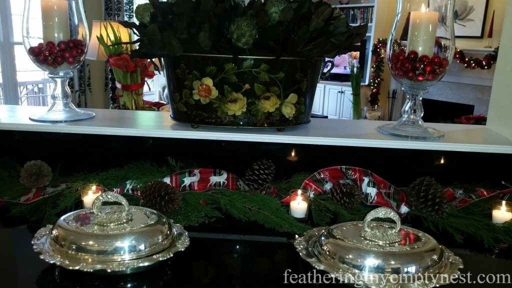 Plaid reindeer ribbon, pine cones, greens and votive candles decorate Christmas buffet --Christmas Centerpiece Conundrum