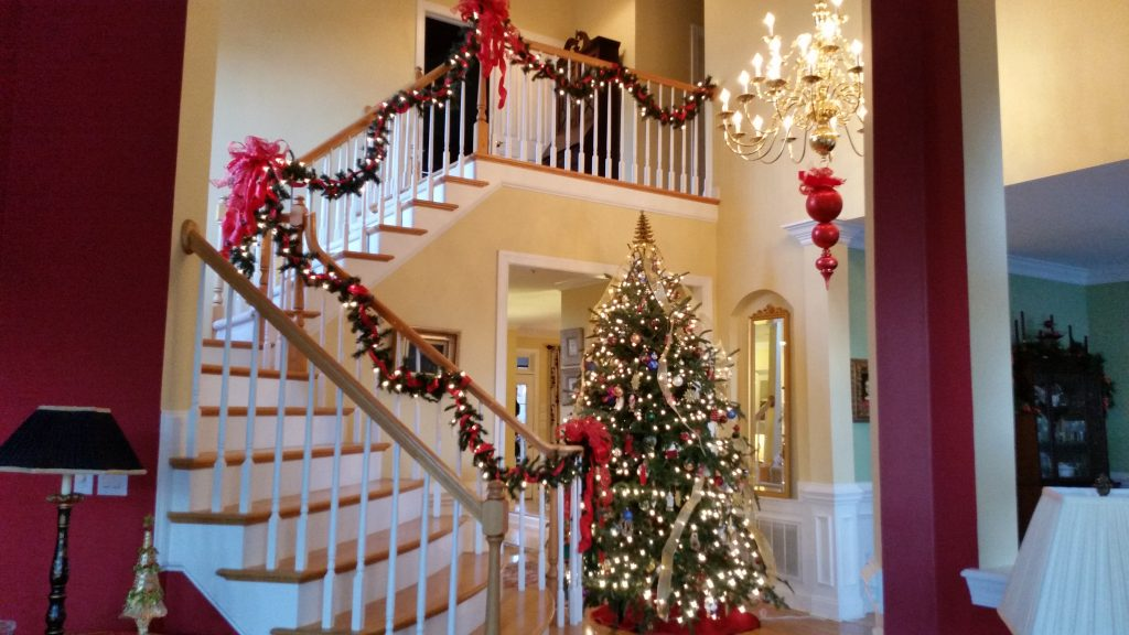 Foyer with lighted garland and crazy big red bows I made to decorate the staircase.