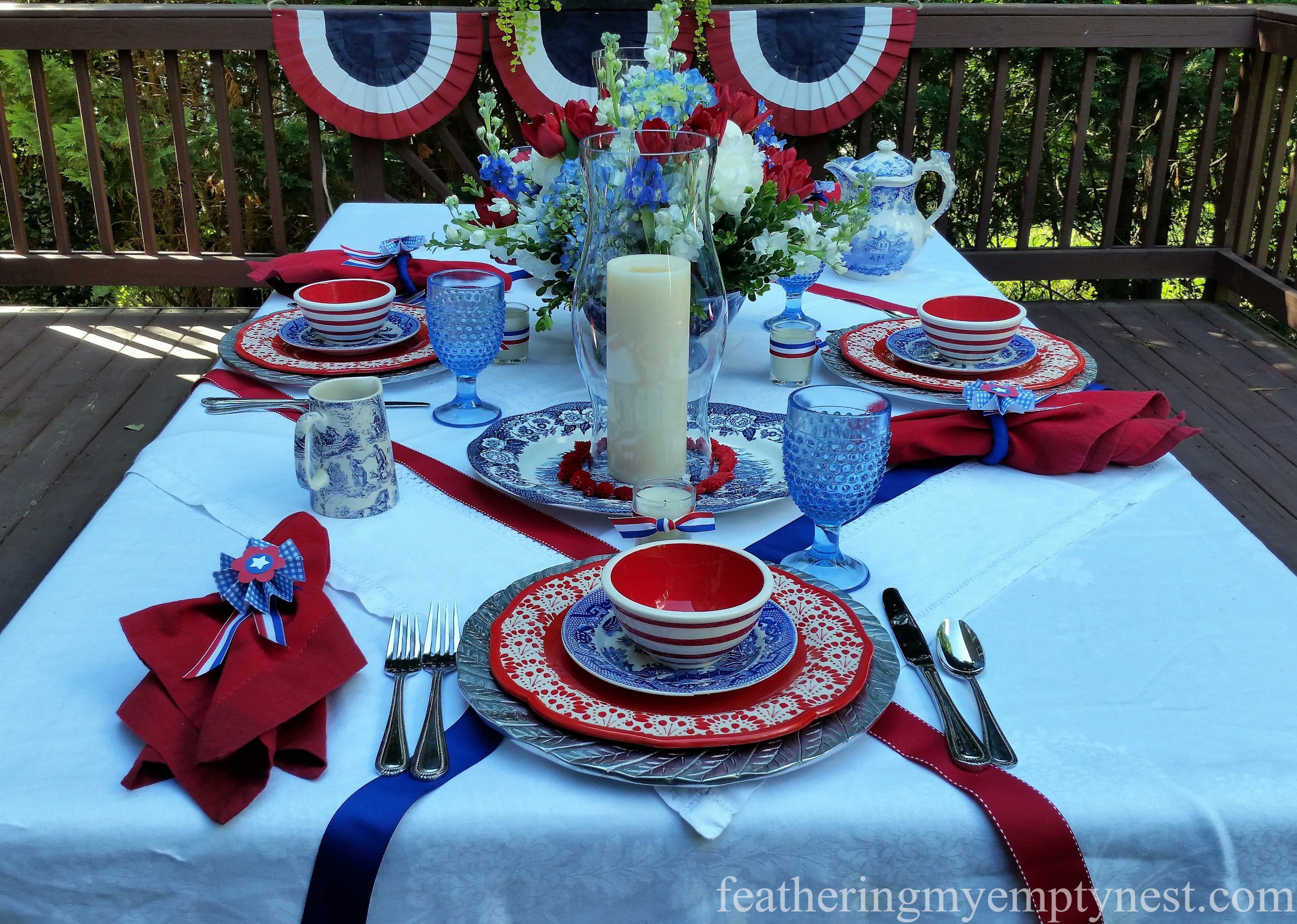 Red and blue ribbon are added to a white linens to make a patriotic tablecloth for and Old-Fashioned 4th of July