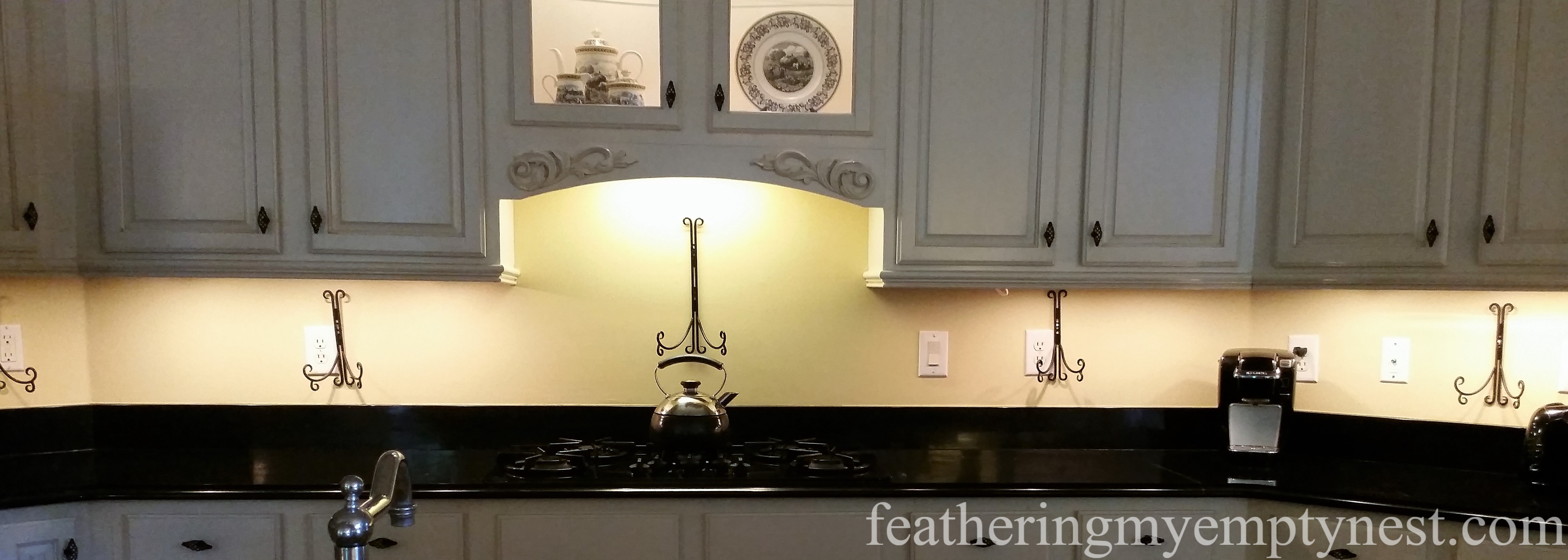 Plate Hanger Easels camouflage a plethora of outlets--Inexpensive Kitchen Updates And Camouflage