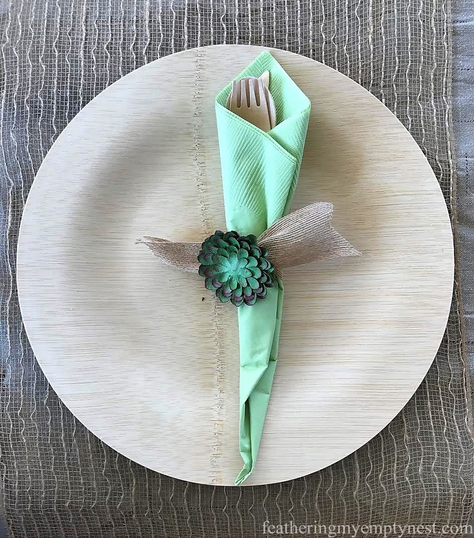 Paper succulent sticker and burlap ribbon serve as a napkin ring for Trendy Succulent-Themed 80th Birthday Party