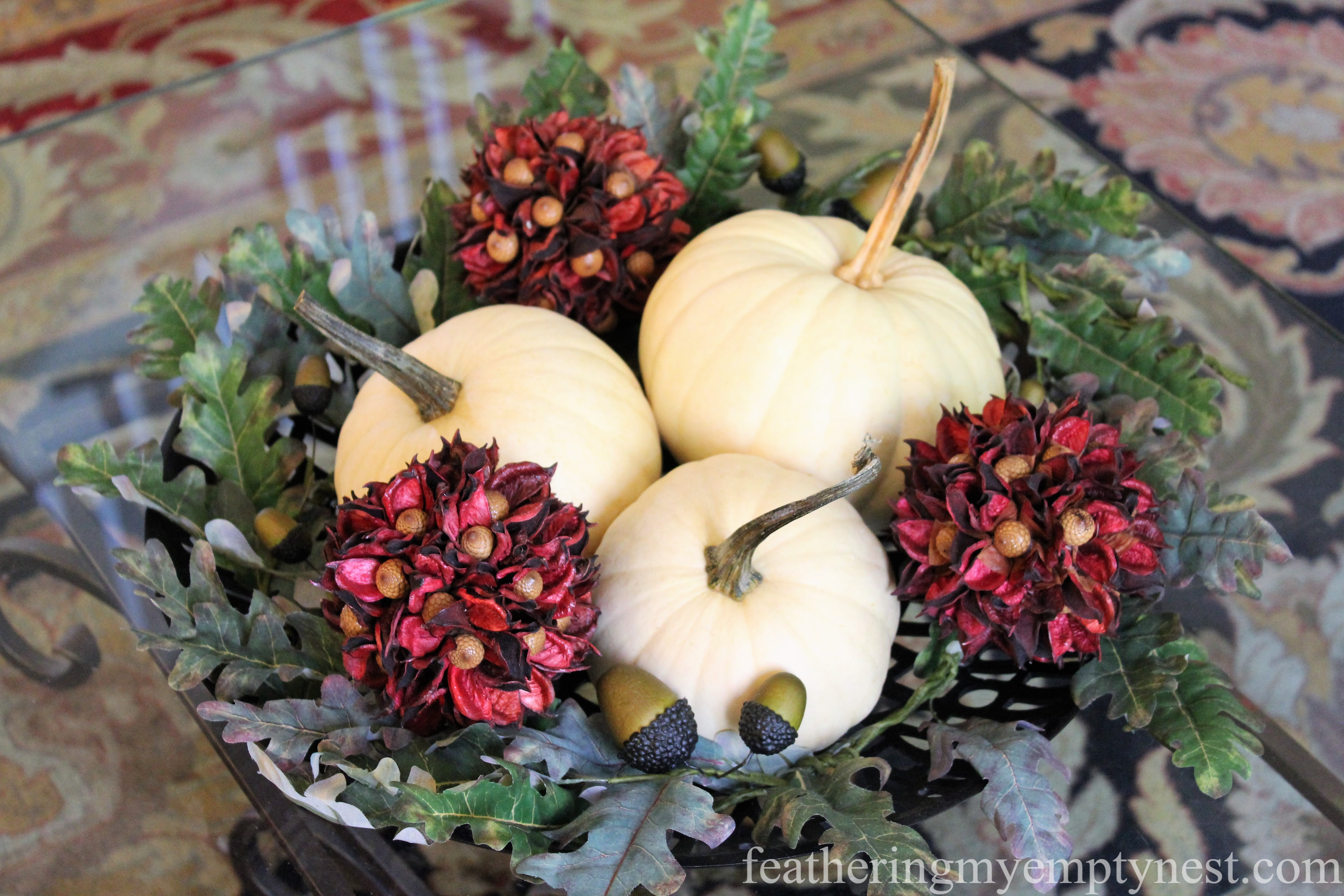 Pumpkins and seed pod balls make up the Fall part of --Easy Fall To Christmas Coffee Table Arrangements