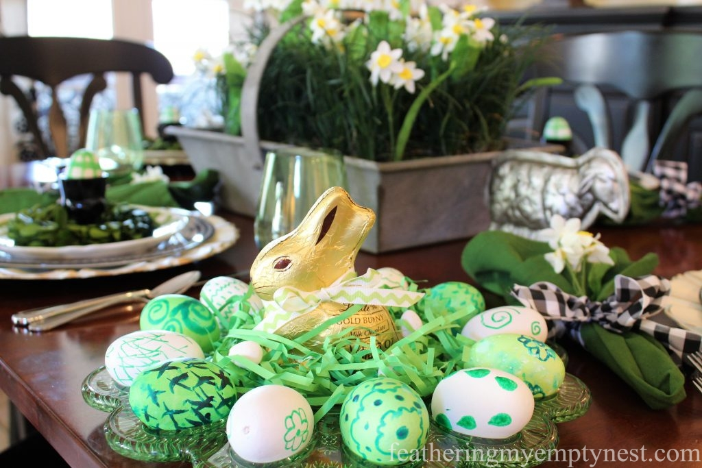 Chocolate bunny sits on a nest of Easter grass and hand-painted Easter eggs --How To Set A Fresh Fun Farmhouse Easter Table