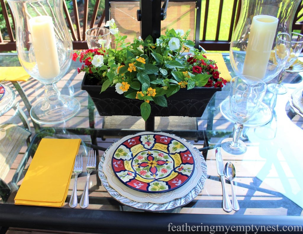 Yellow and red place setting coordinates with the summer flowers in the planters on the deck.