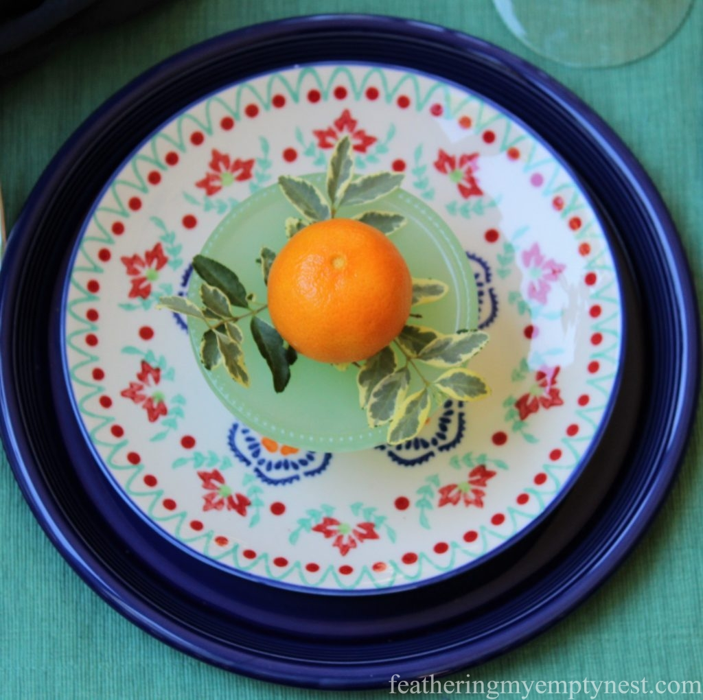 A Mandarin orange adds a pop of color to the plate stack on An Impromptu Outdoor Table For Two