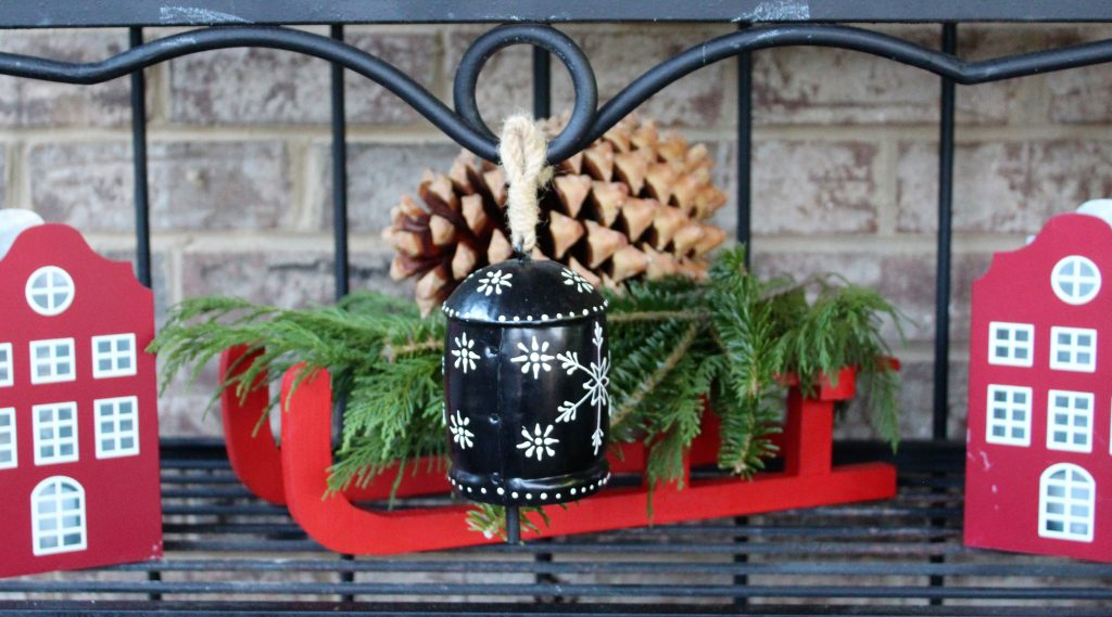 A red wooden sleigh is loaded down with greens and a giant Coulter pine cone  --Christmas Decorating Odds & Ends