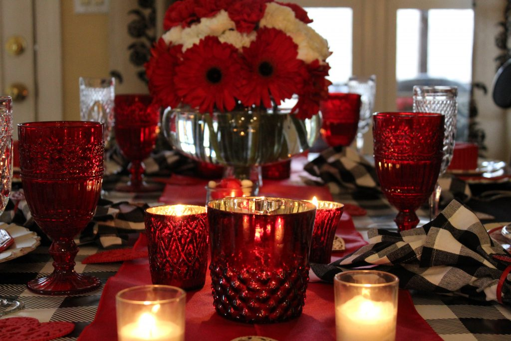 Red mercury glass votives and pressed glass goblets add color and sparkle to a special Valentine's dinner table.