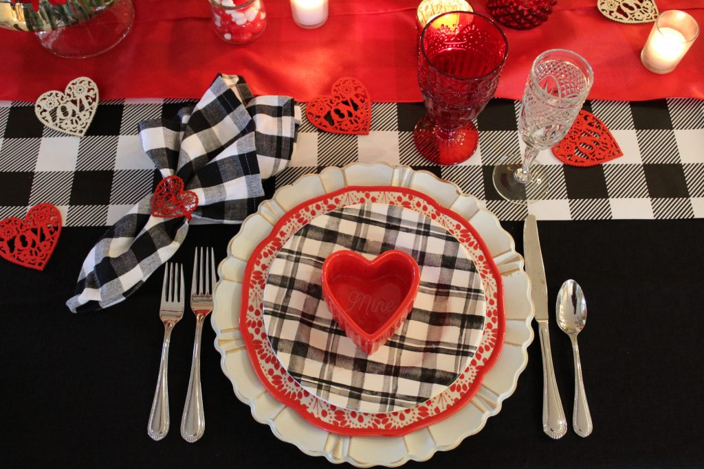 Layered plates in alternating colors of white, black and red make a fun festive Valentine's table setting.