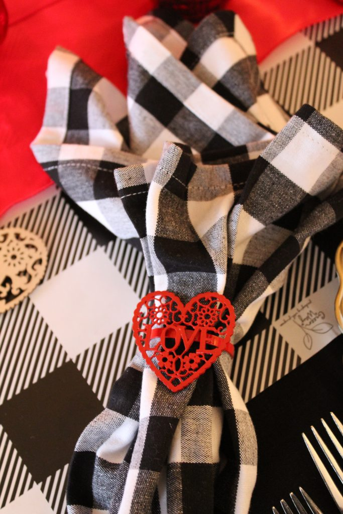 Lacy red heart napkin rings pop against bold buffalo plaid table linens in this fun festive Valentine's tablescape.