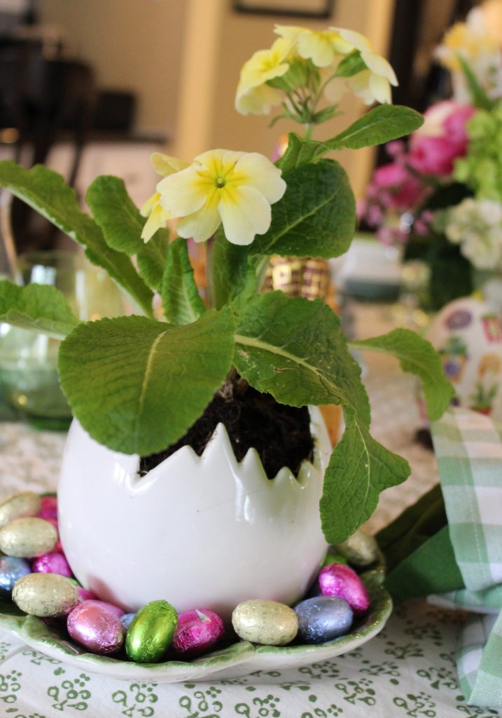 A Grown-up Easter Candy Tablescape--Primroses planted in cracked egg pots add a whimsical touch to the table.