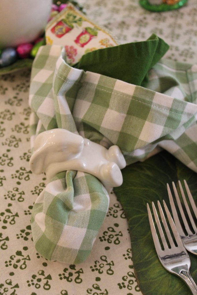 A Grown-up Easter Candy Tablescape--reclining bunny napkin ring wraps around green solid and gingham napkins.
