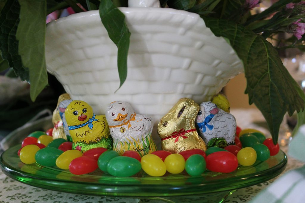 A Grown-up Easter Candy Tablescape--Jelly beans and Lindt Chocolate Bunnies & Friends play ring around the rosie on a green depression glass cake plate beneath a flower basket