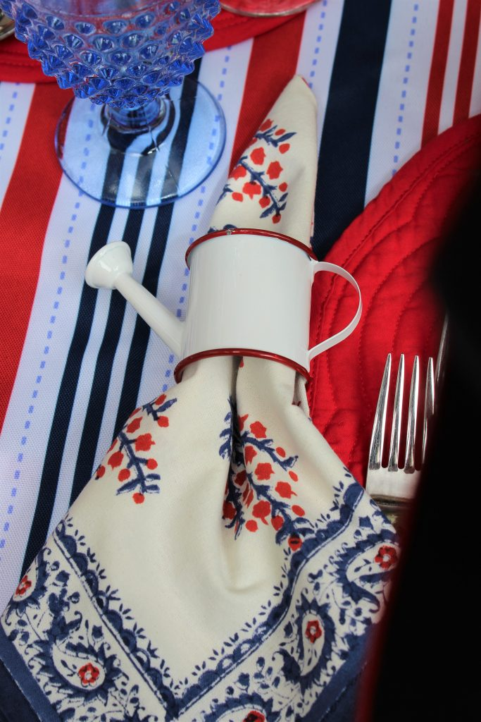 Red, white, and blue hand-blocked napkins in watering can napkin rings are perfect for a patriotic picnic.