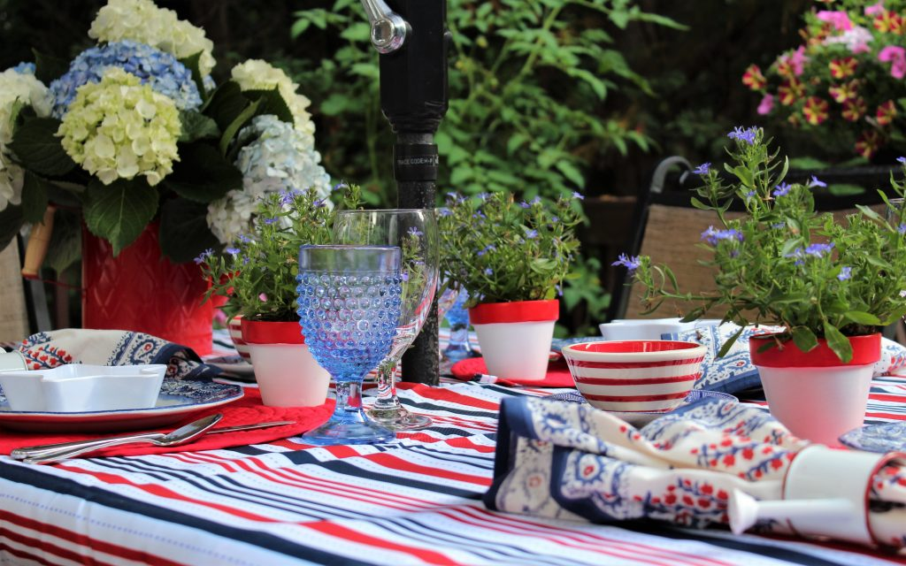 A patriotic tablescape with lots of flowers and stripes.