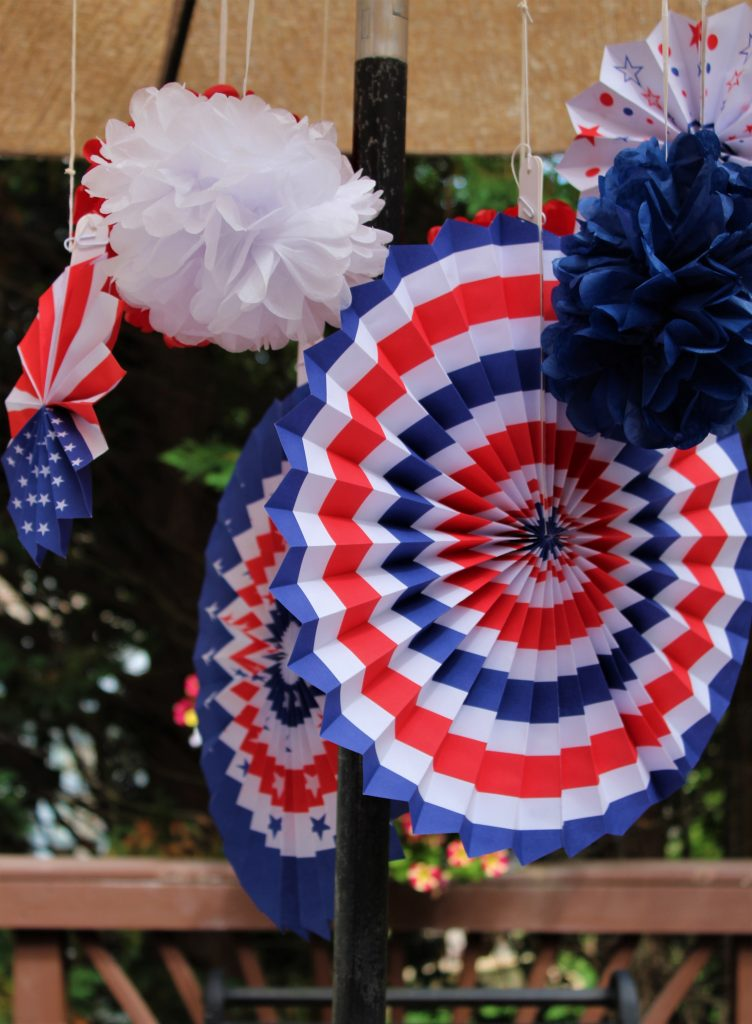 Inexpensive patriotic paper decorations add a festive touch when hung from the umbrella of this patriotic tablescape.